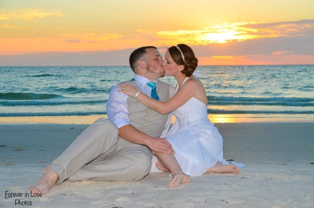 Clearwater beach wedding couple sitting on the beach kissing