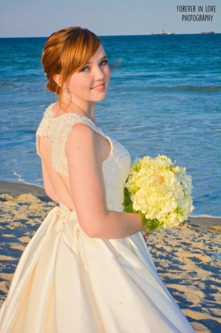 Bride on the Florida beach holding yellow bouquet