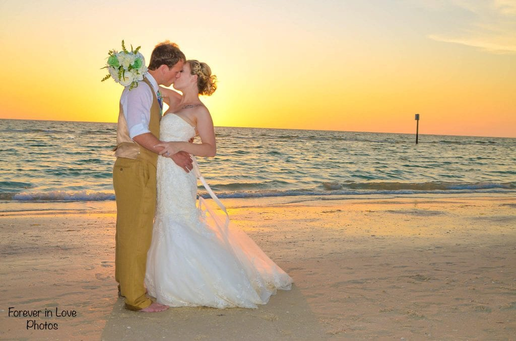 Barefoot wedding couple kisses at sunset on Clearwater Beach, FL