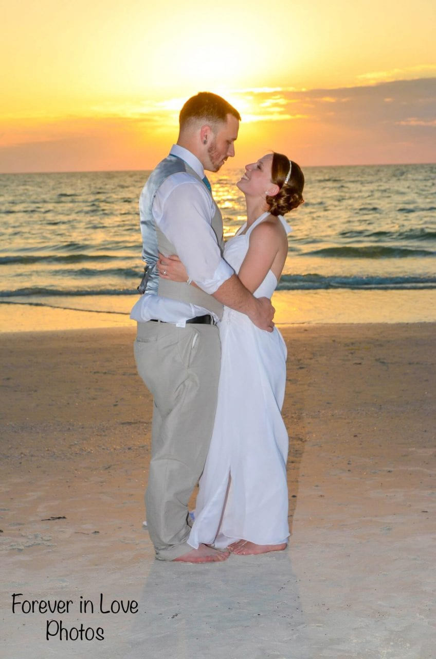 Wedding couple kissing at sunset on St. Pete Beach, FL