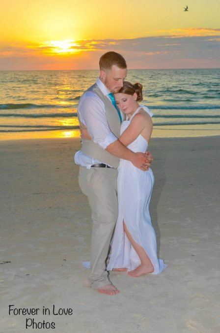 Bride and groom hugging at sunset Gulf beach wedding in Florida