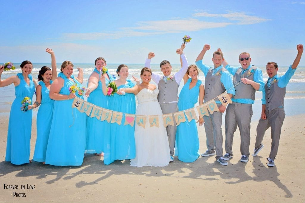 A bridal party celebrates with a Just Married photo at our Cocoa Beach Weddings.