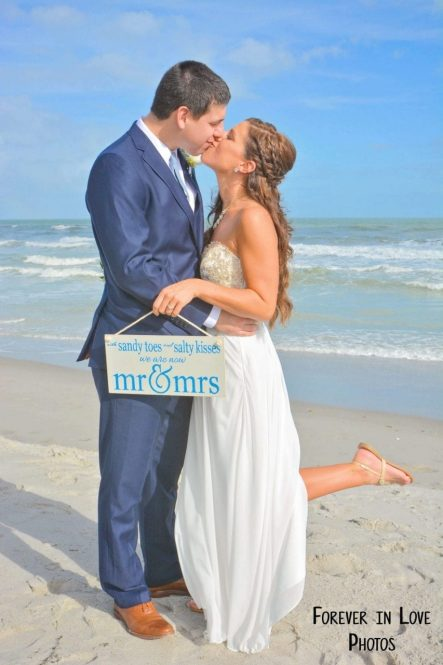 Couple kissing on the beach with just married sign
