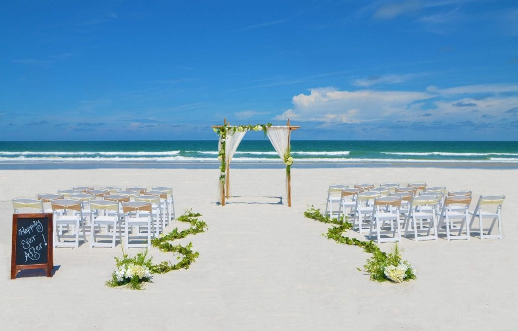 Floral wedding arch with white chairs and greenery on Siesta Key Beach