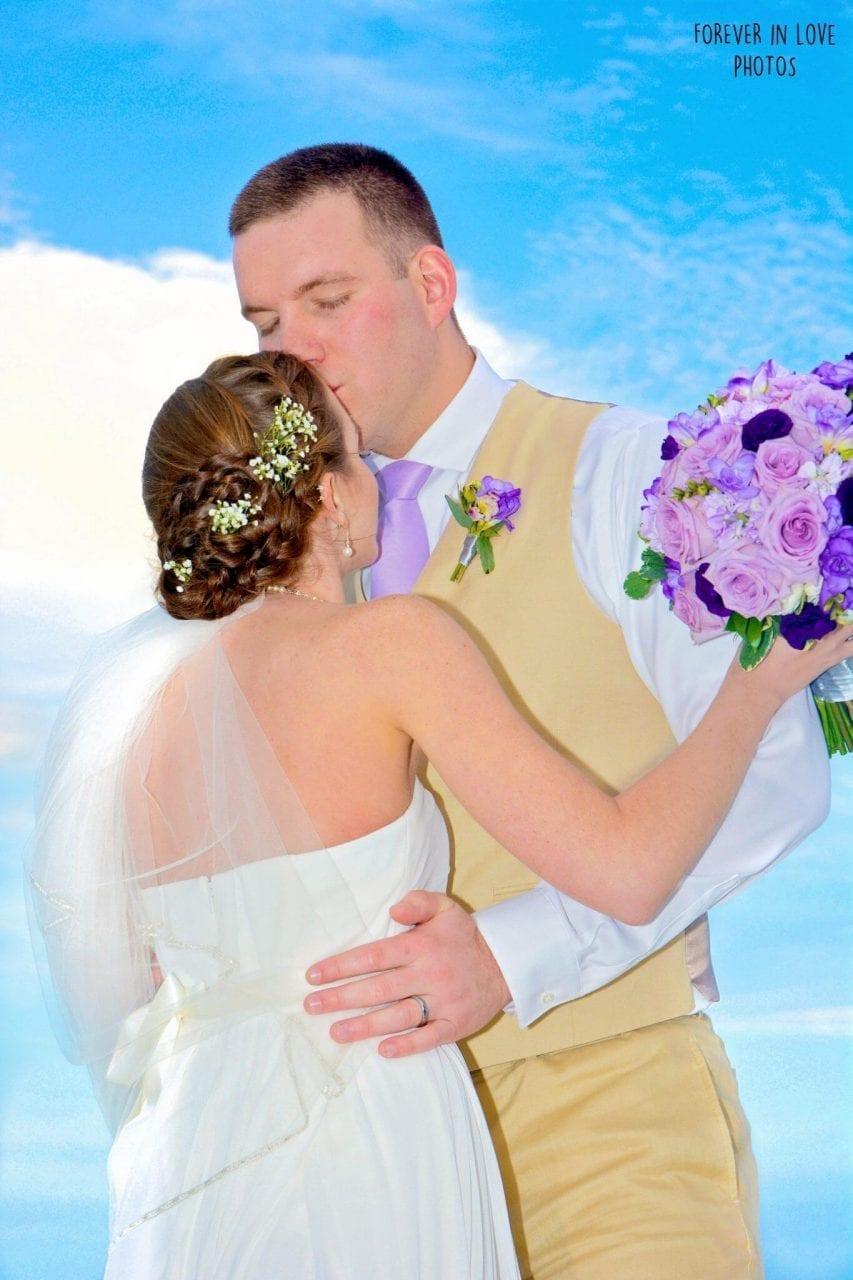 Groom kissing bride at beach wedding