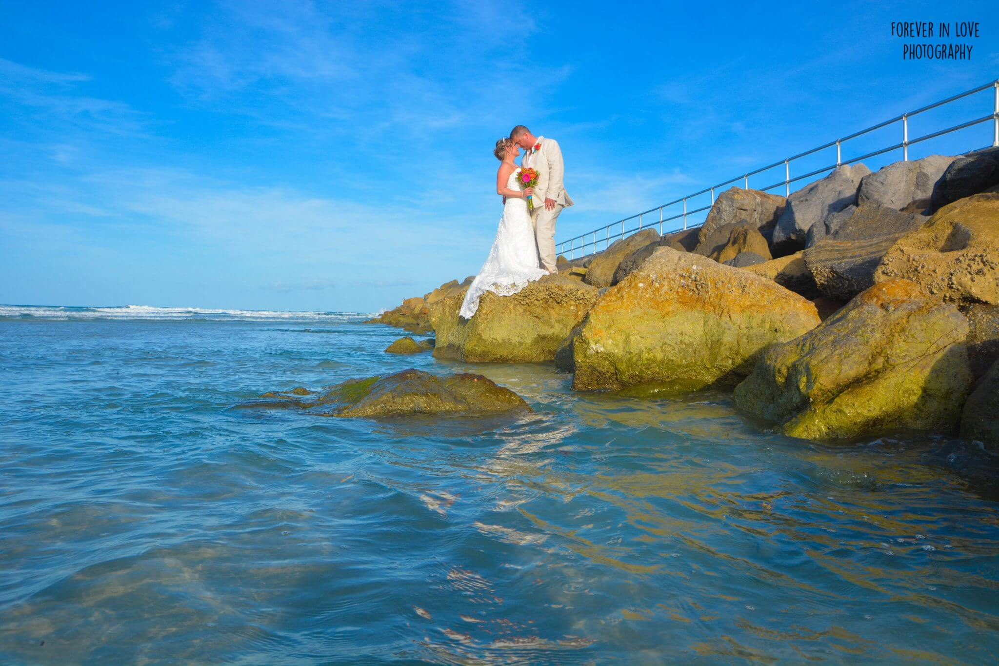 Couple kissing on rocks at beach wedding