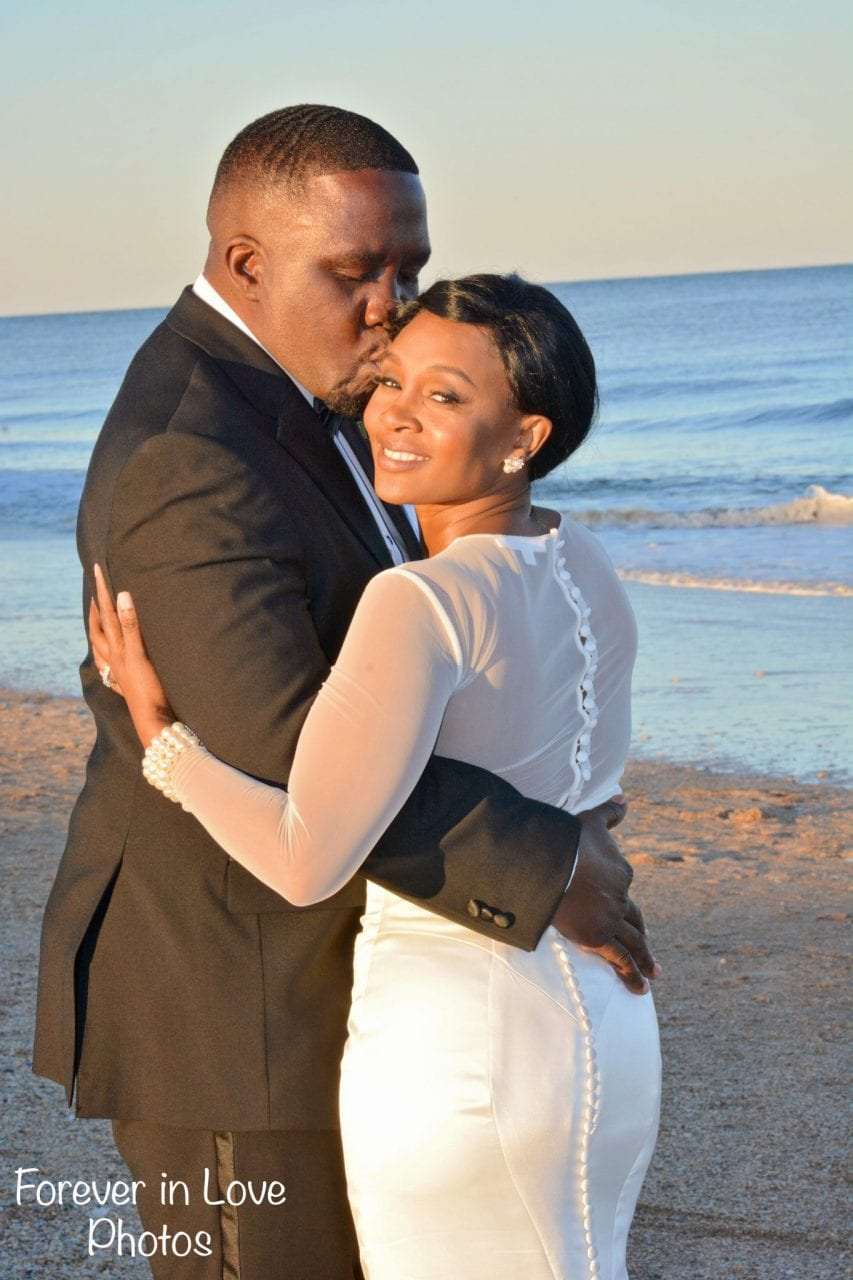 African American couple just married on the beach.
