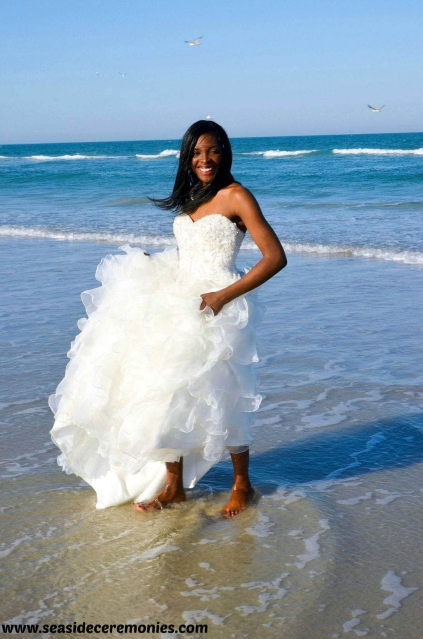 Gay bride on the beach wading in the ocean water