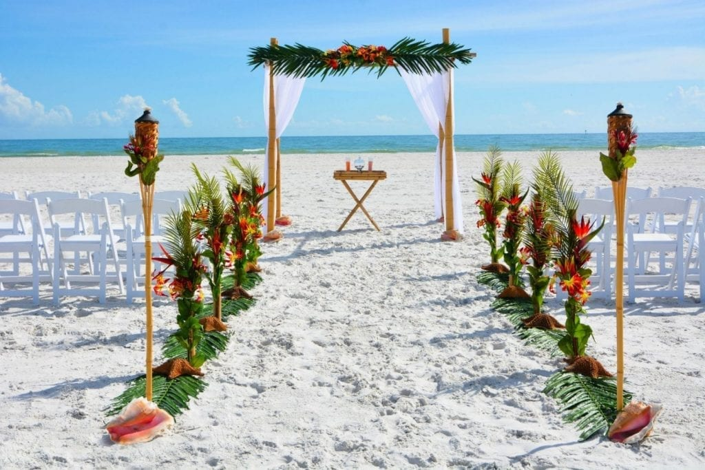 Florida Beach Wedding Package with tropical decor, chairs set up on beach.