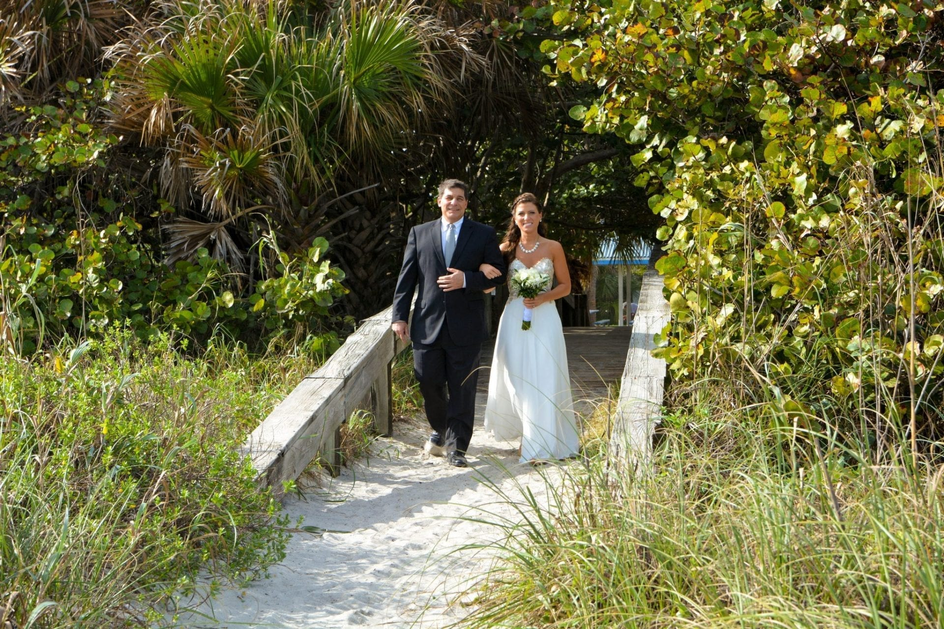 Couple on beach walkway after wedding ceremony in Cherie Down Park, FL