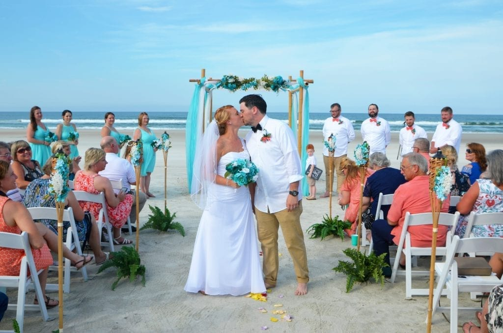 At a Florida Beach Wedding this couple has their first kiss with a teal wedding arch