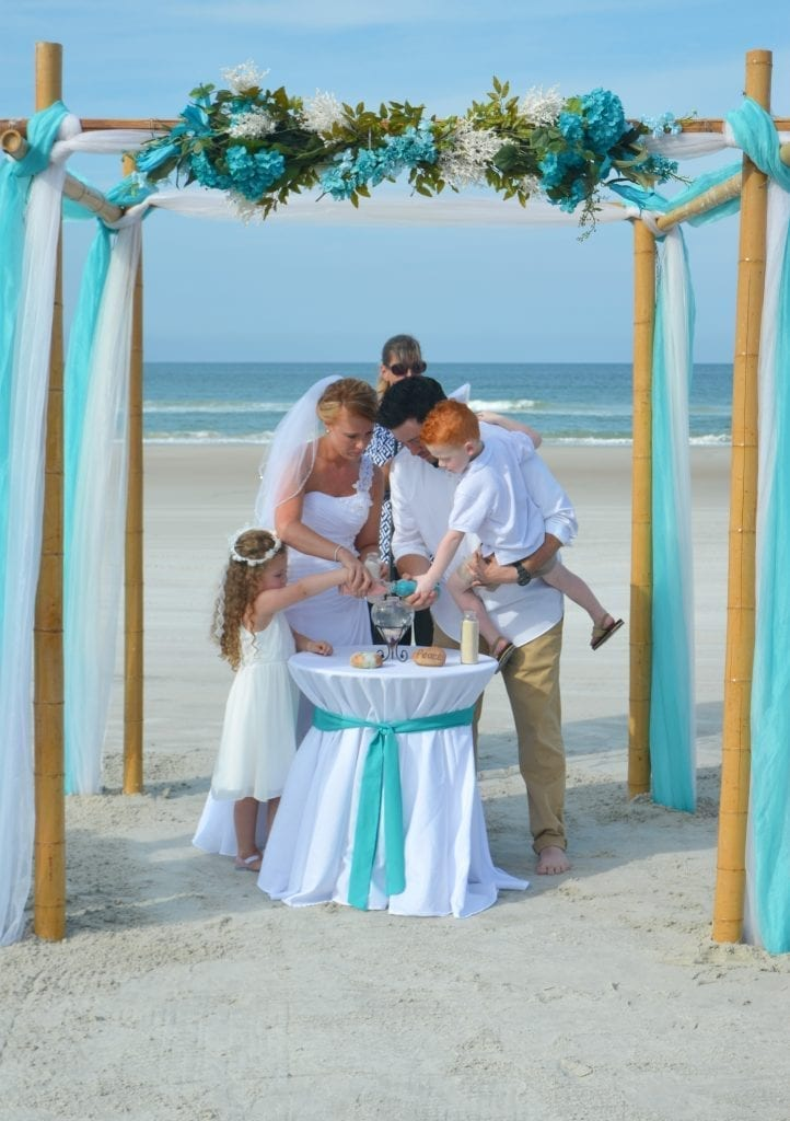 This family joins together at a sand ceremony at a Florida Wedding on the beach.