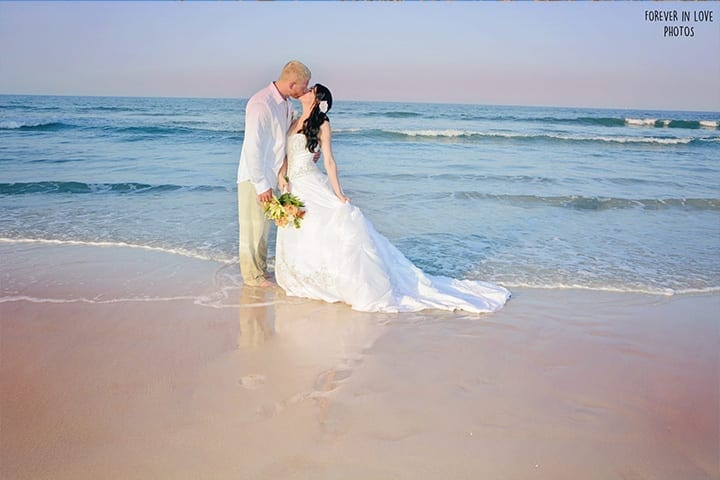 Daytona Beach wedding couple kissing after vows in the ocean surf