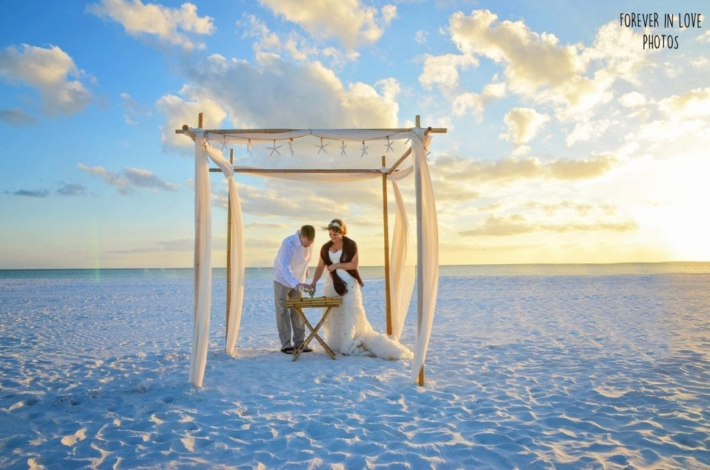 Couple eloping on Indian Rocks Beach under wedding arbor