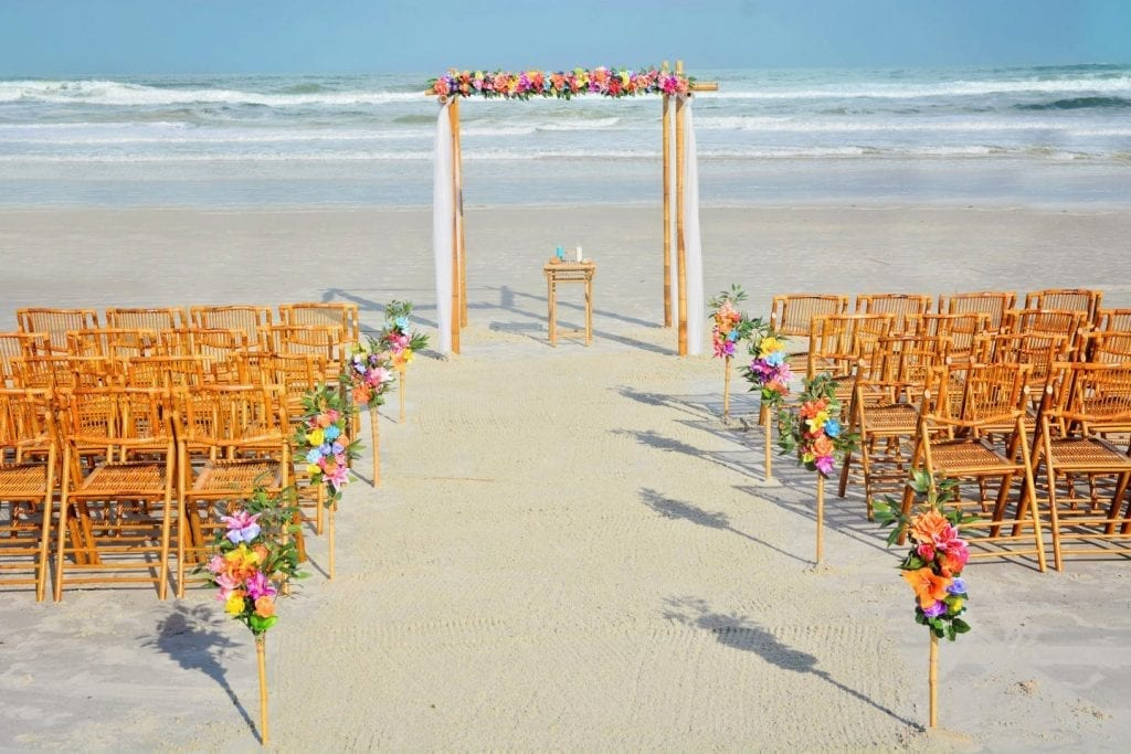 Bamboo chairs and tropical flowers on bamboo wedding arch on Daytona Beach