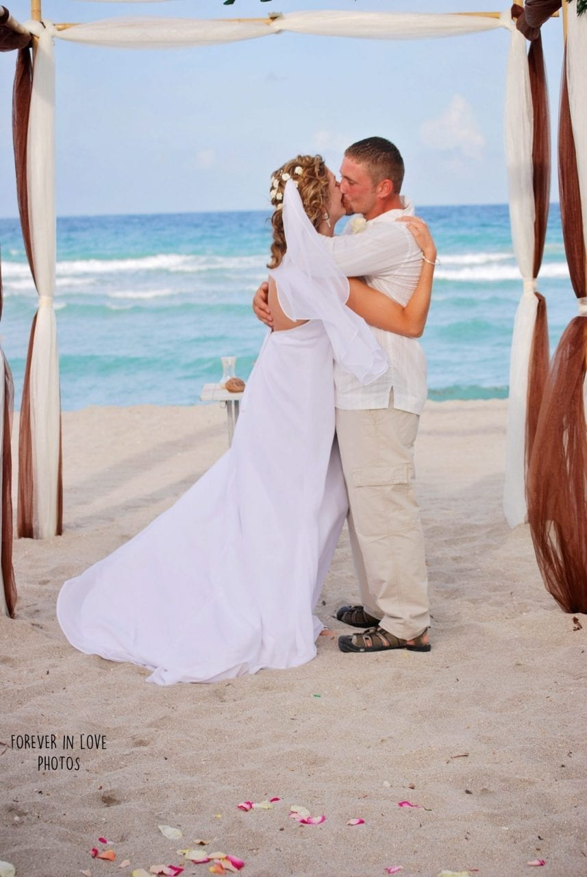 Couple kissing under wedding arch on South Beach, Miami