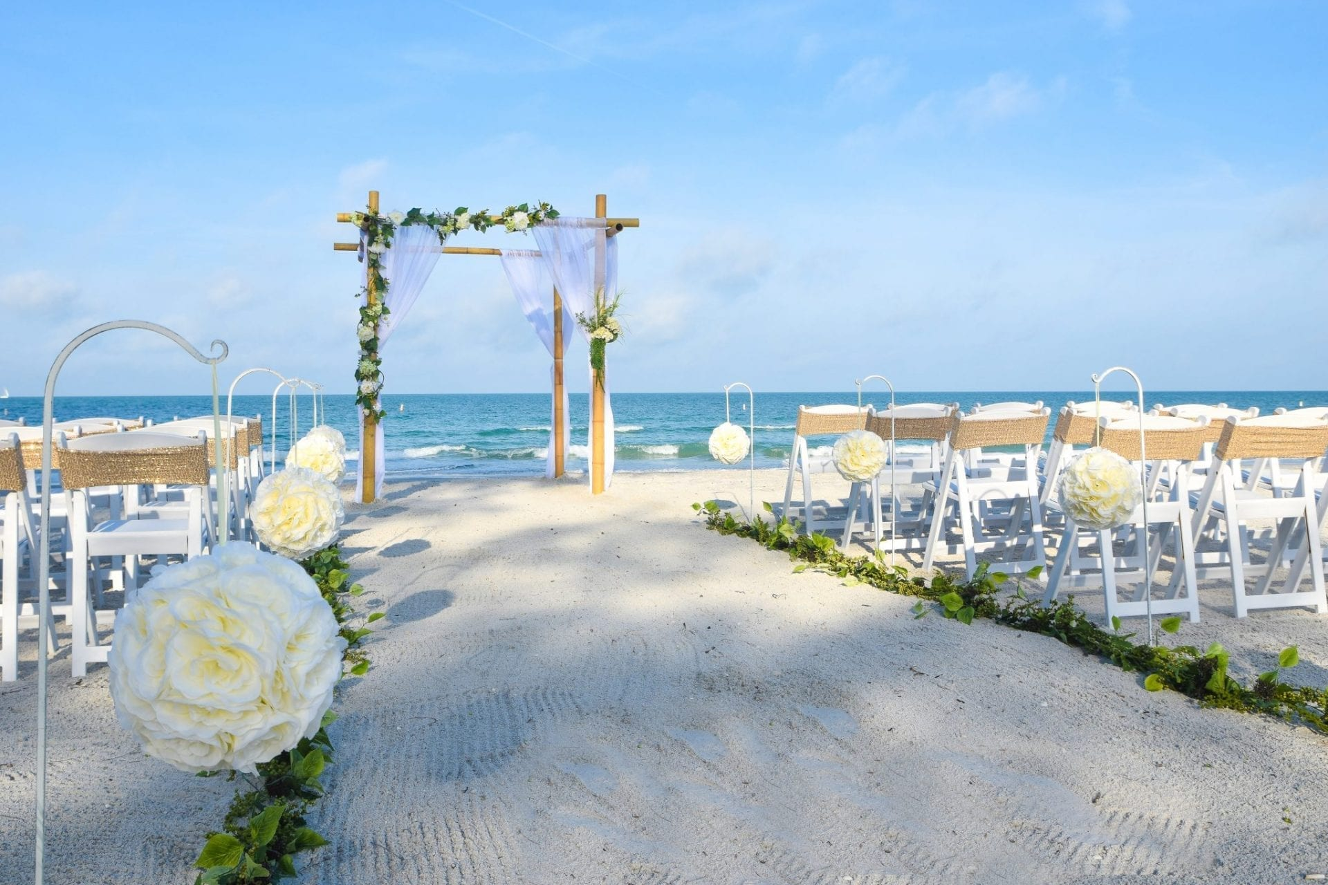 Floral Gulf beach wedding arch and chairs