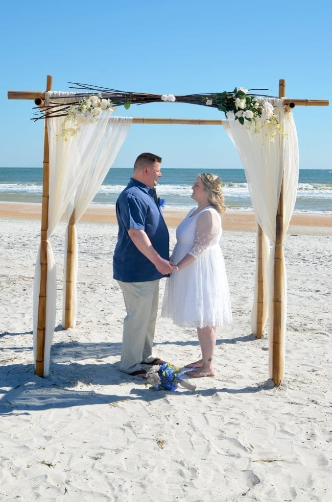 Couple elopes under bamboo arch on Daytona Beach, FL