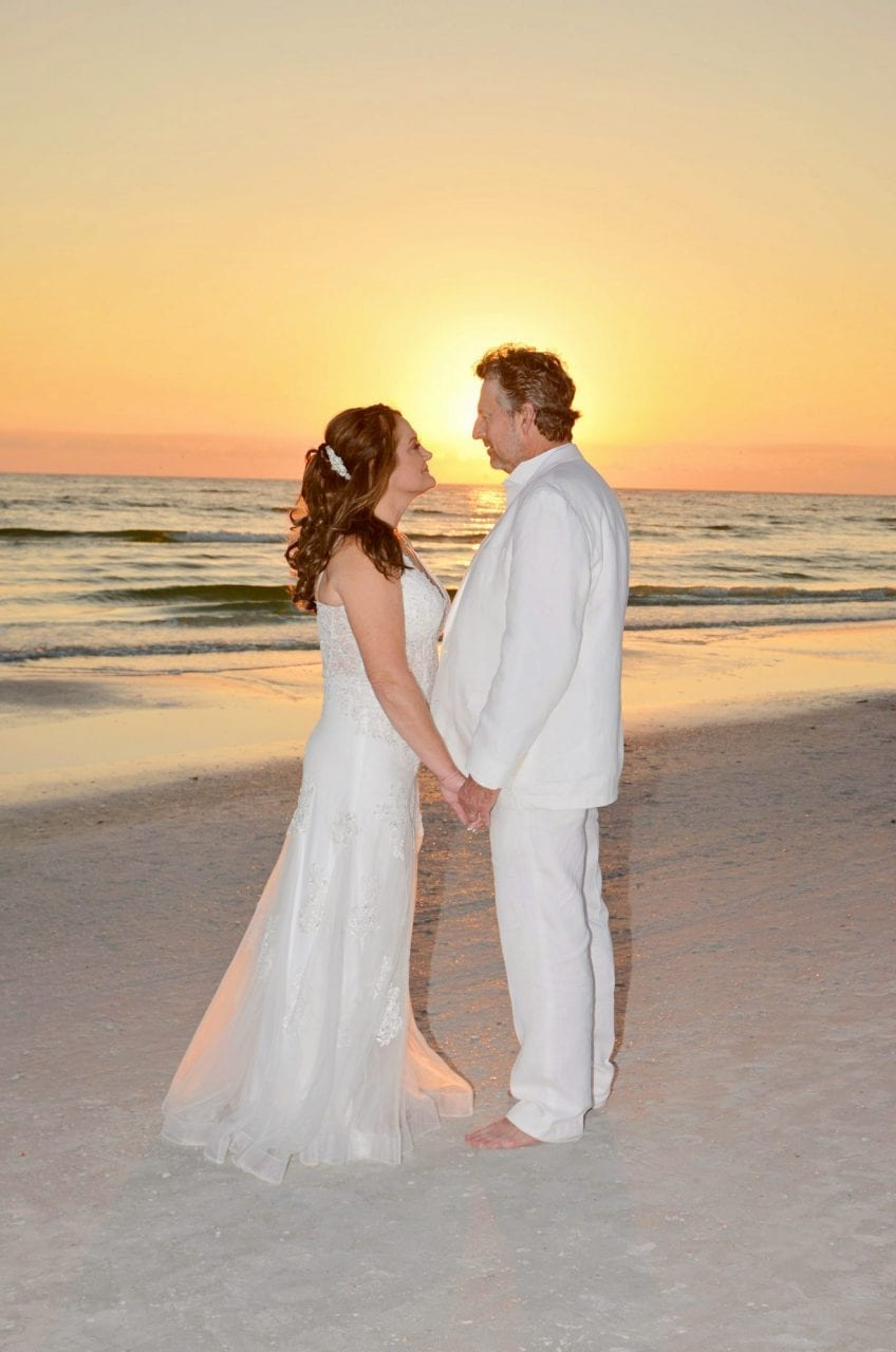 Wedding couple holding hands in sunset on beach