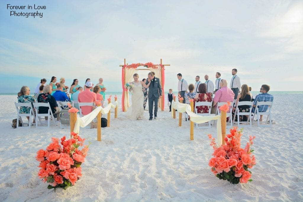 Coral flowers and wedding arch on white sand beach with couple