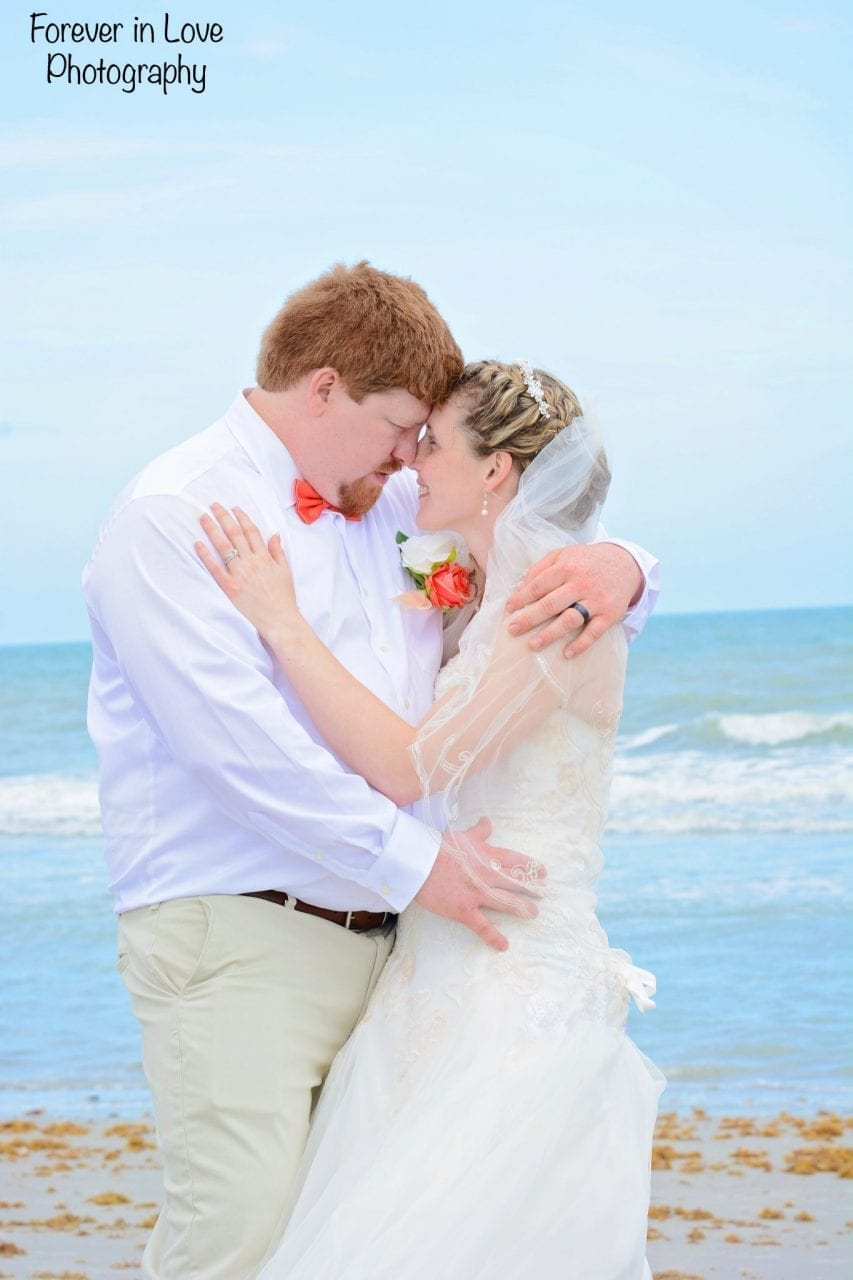 Couple just married hugging on the beach.