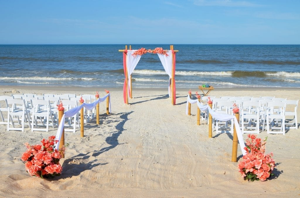 Coral and white wedding decor set up on Daytona Beach.