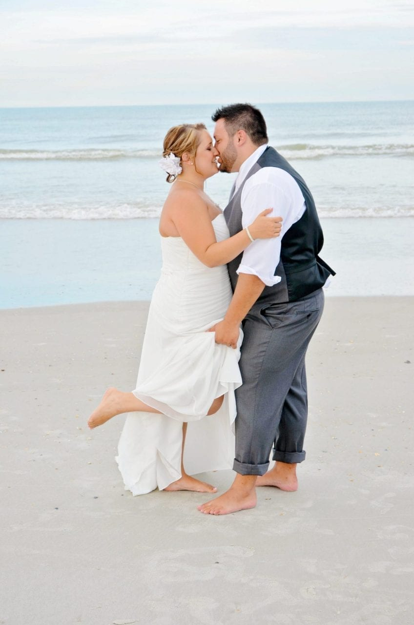 Bride and groom kissing on Jacksonville beach after wedding