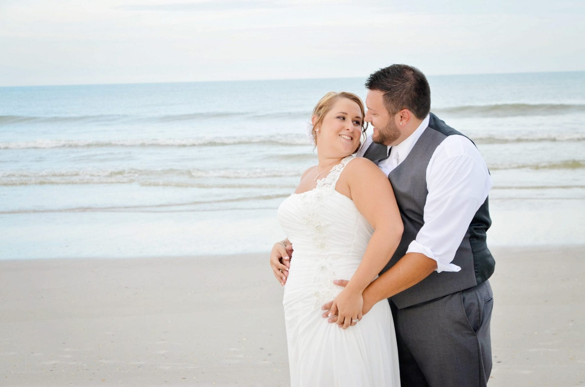 Bride and groom hugging on Jacksonville beach