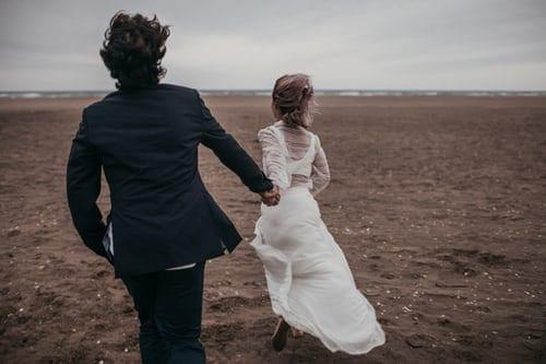 Couple running towards beach for wedding