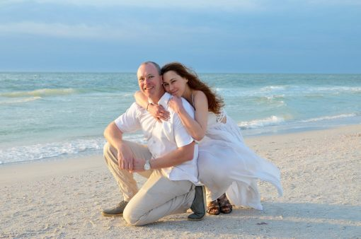 Couple kneeling on Fort Myers Beach after their wedding vows