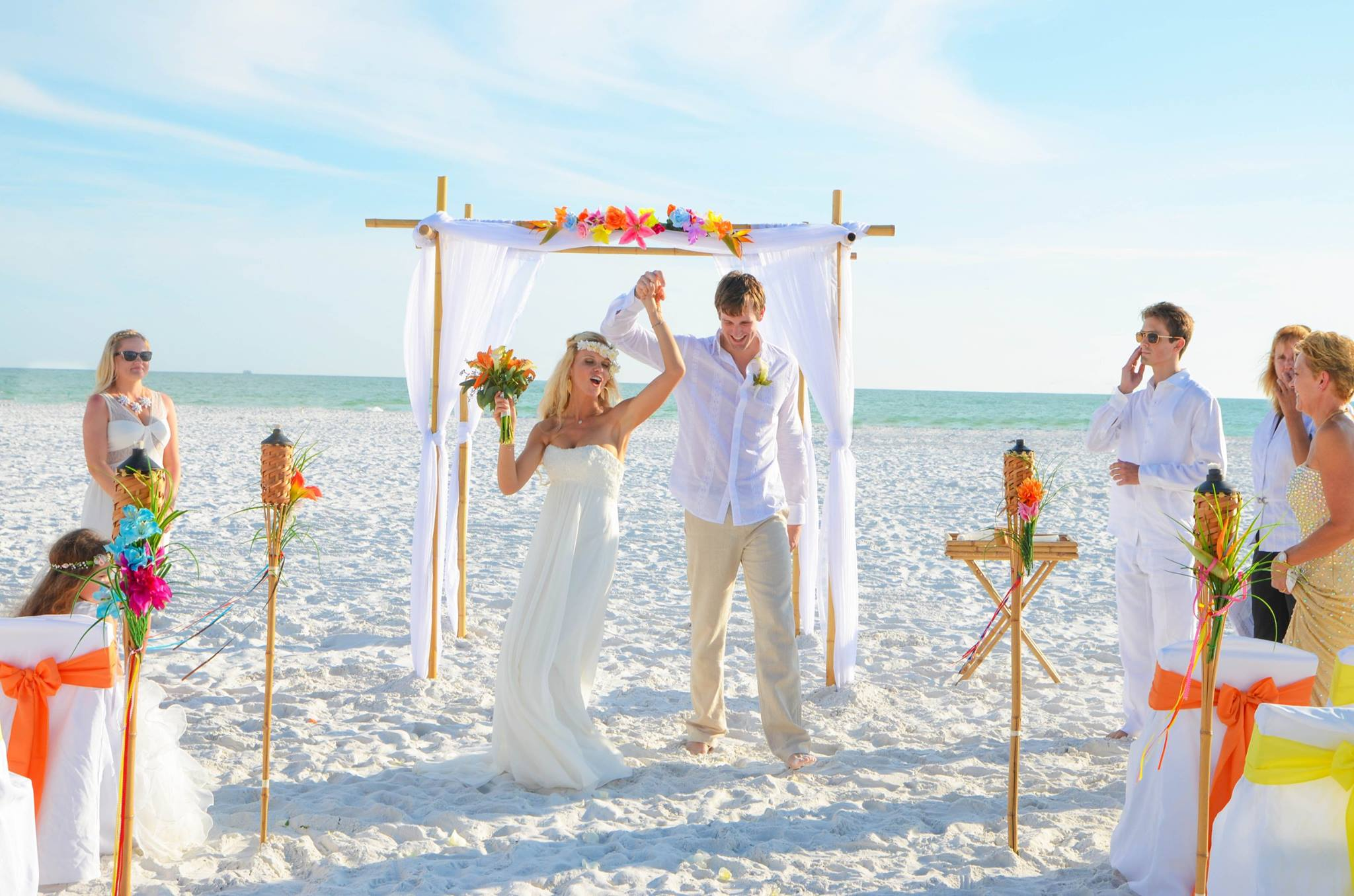 Wedding couple on the beach under tropical arch