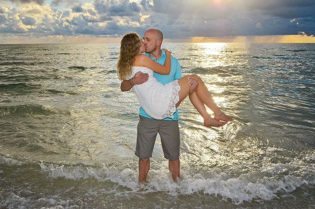 Wedding couple kisses at sunset in the water