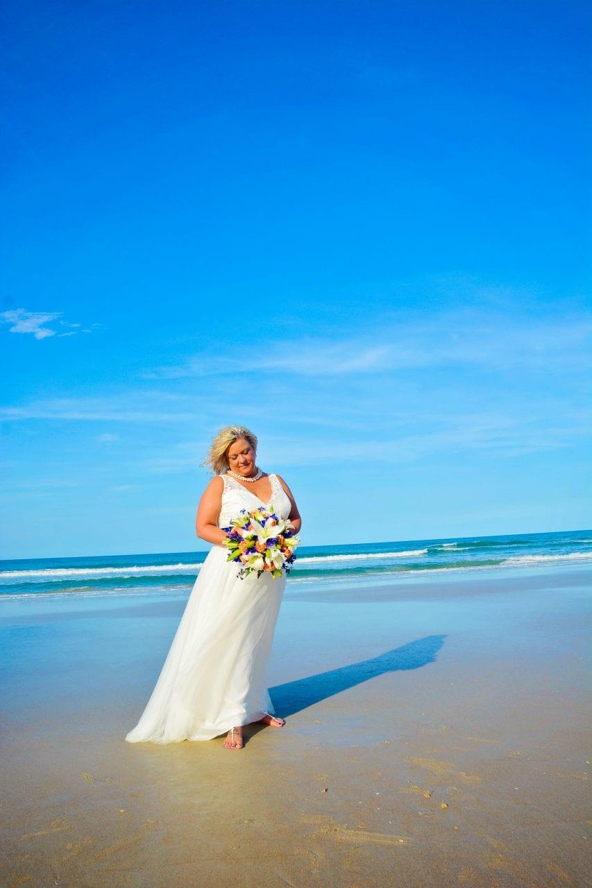 Bride holding flowers on Daytona beach near water