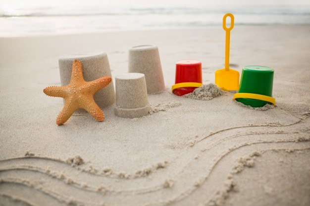 Bucket in sand with starfish