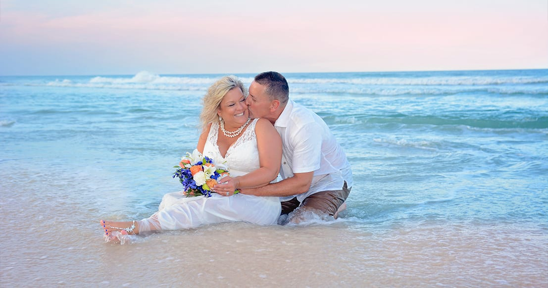 Wedding couple posing on beach in the Atlantic surf.