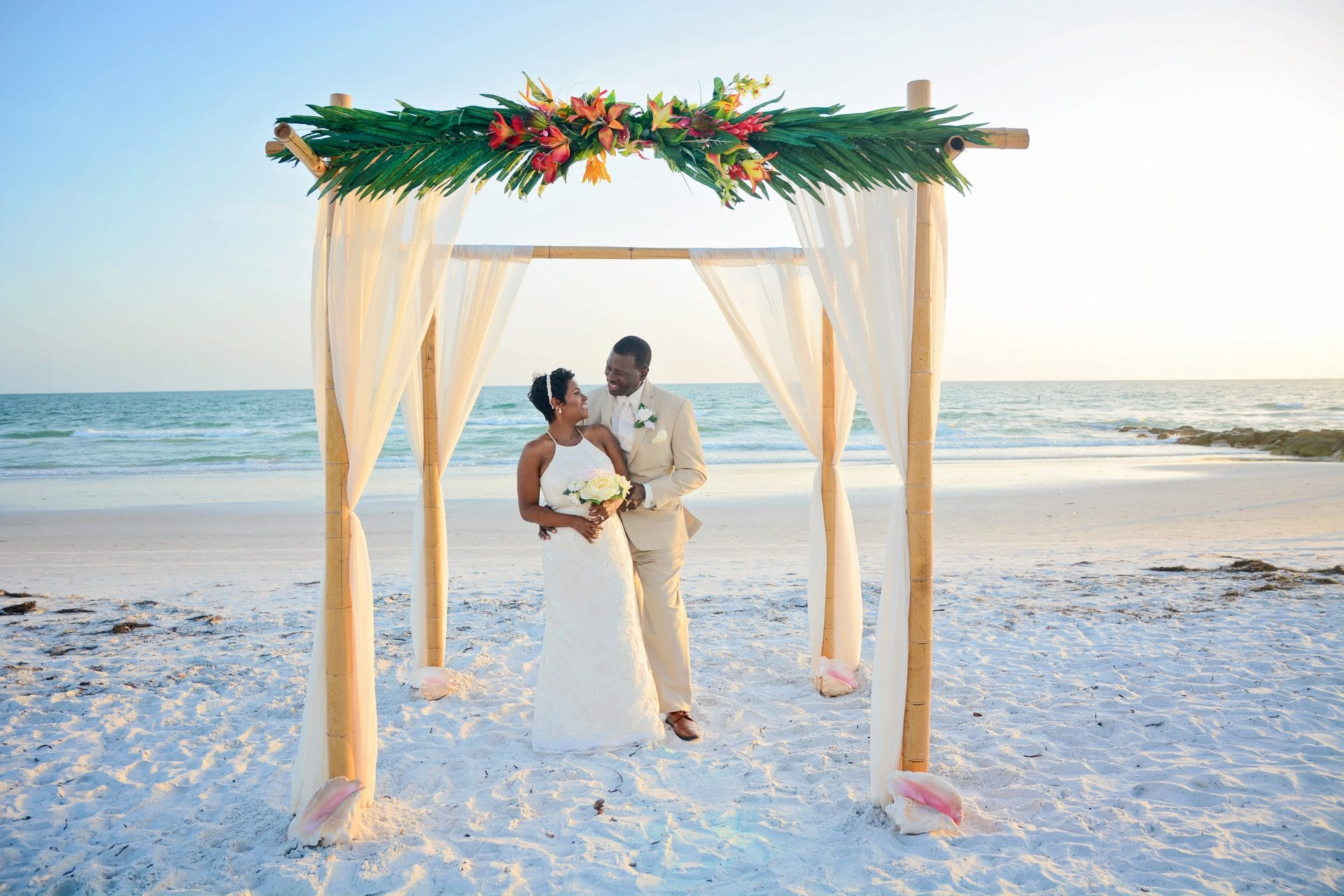 Couple saying vows under beach wedding canopy