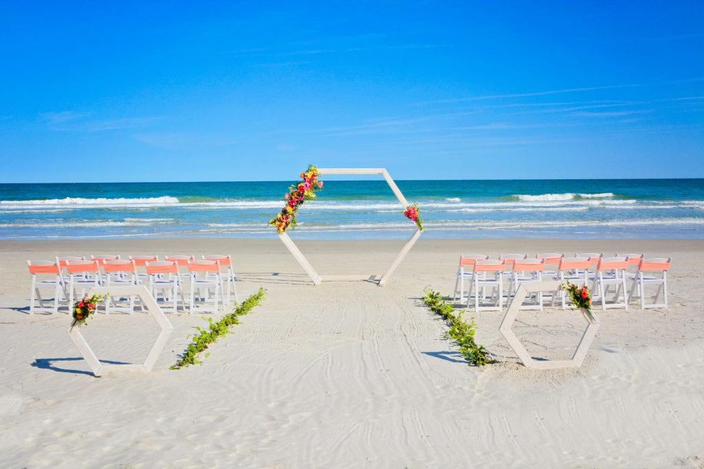 Tropical geometric wedding arch set up for a Gulf beach wedding in Siesta Key, FL