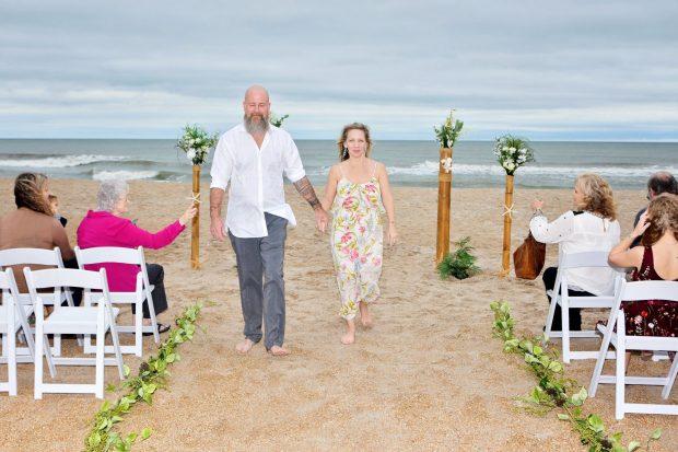 Couple walks down a beach aisle at an ocean wedding