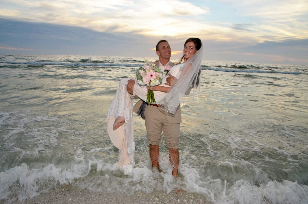 Married couple in the surf after beach wedding