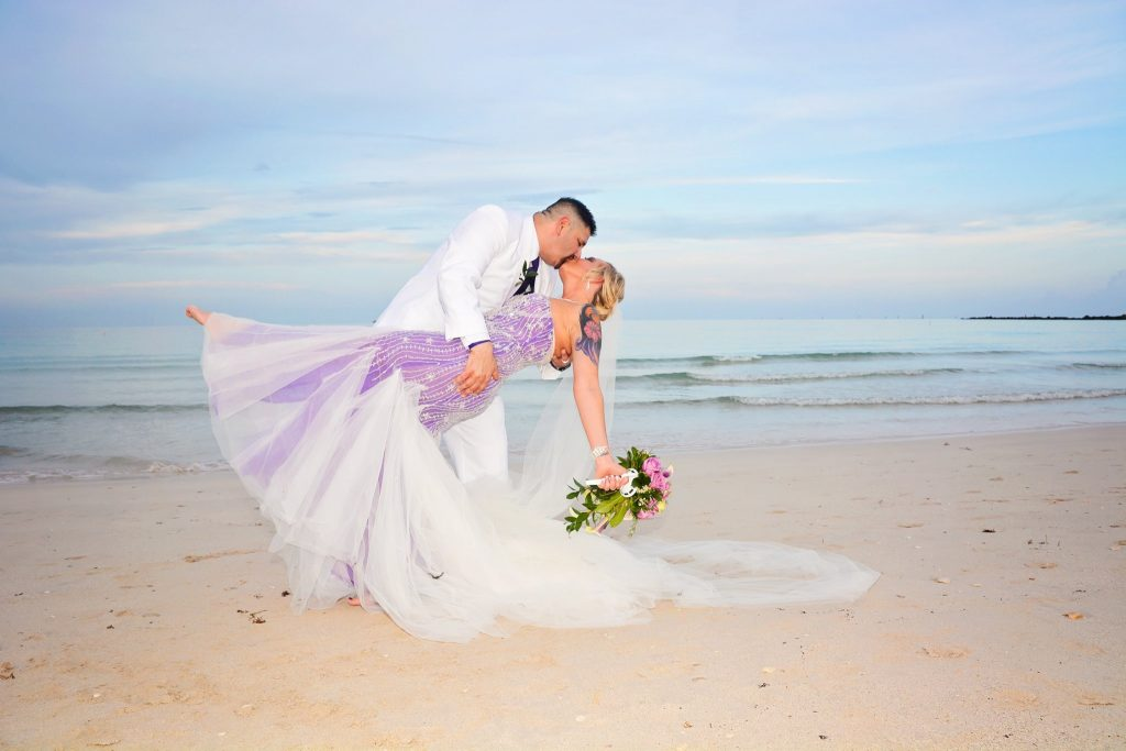 Couple Kisses after Miami Beach Wedding on white sand