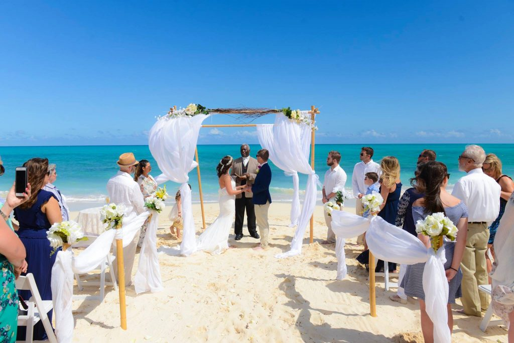 Couple married on Sand Key Beach Florida under white wedding arch