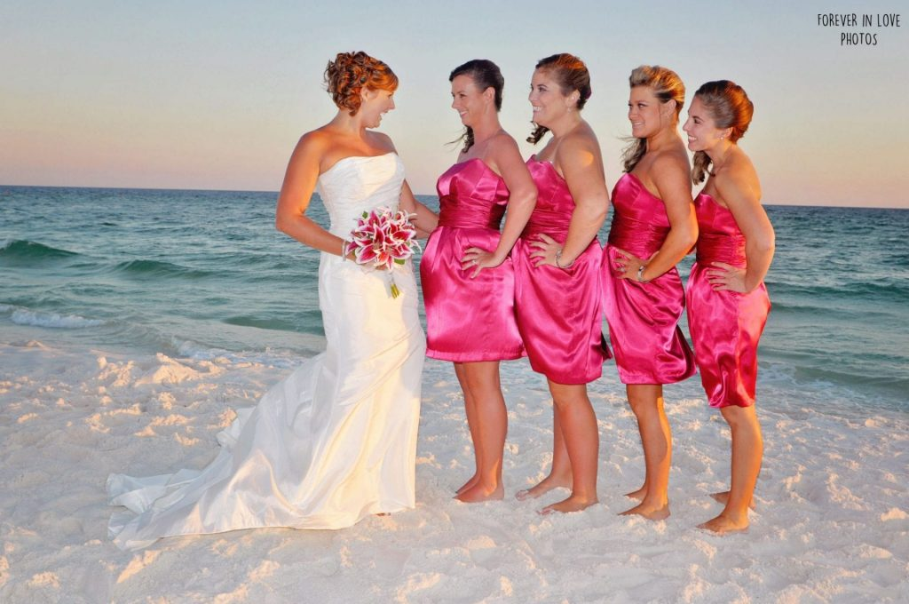 4 bridesmaids in pink satin stand with beach bride