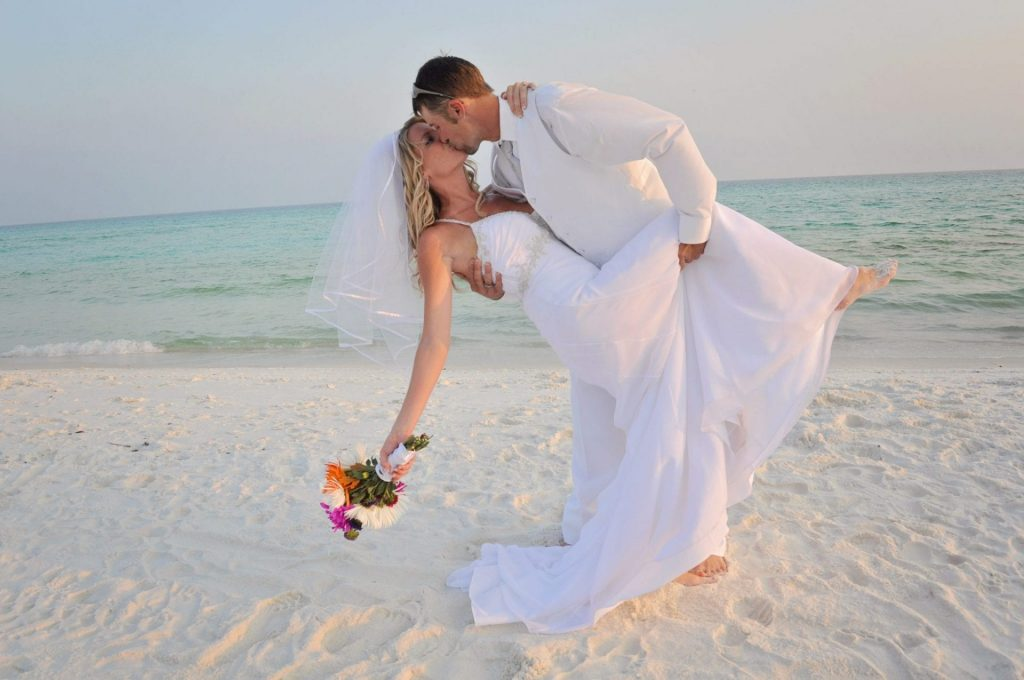 Destin Beach couple just married kisses on the Gulf beach