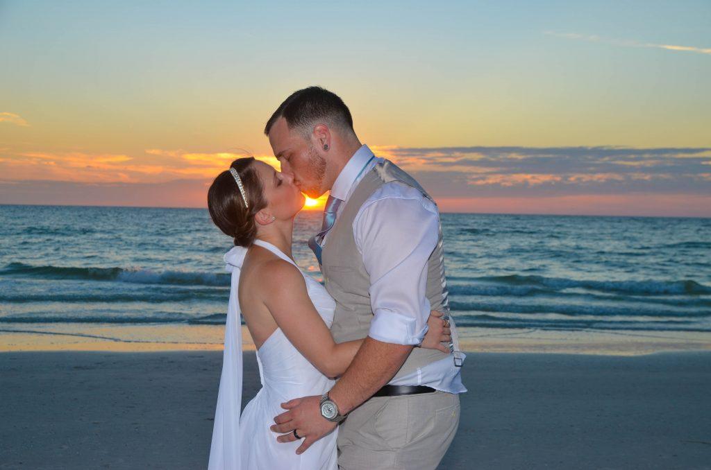 Couple kisses at sunset at Siesta Key wedding ceremony