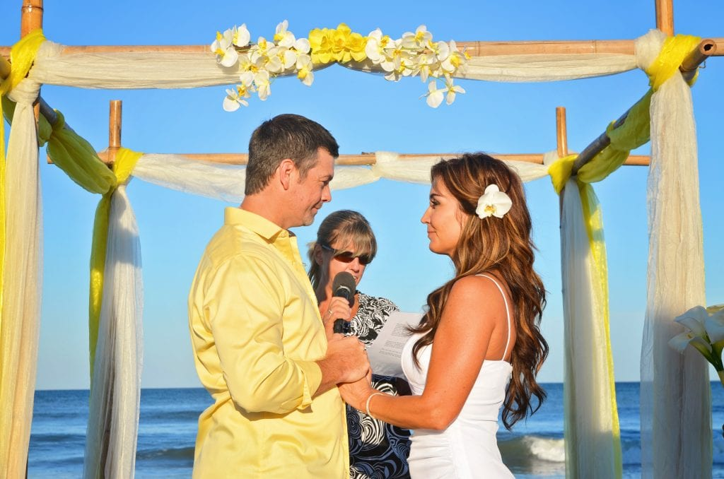 Yellow flowers and fabric on bamboo wedding arch with couple saying vows