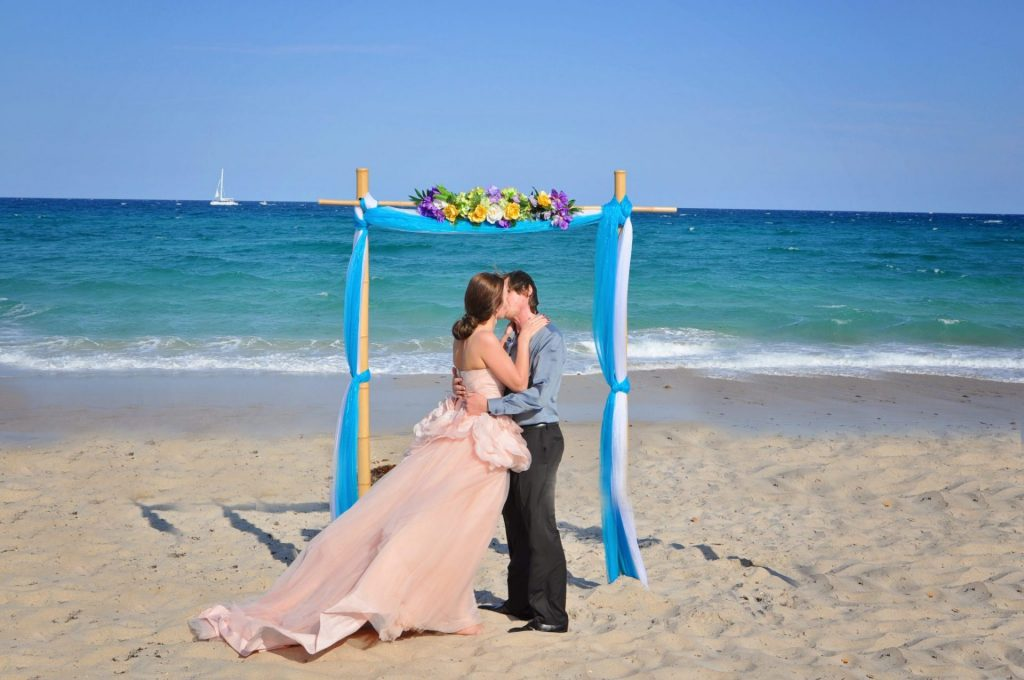 Couple kisses after marriage ceremony on Boynton Beach, FL