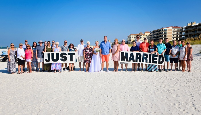 Clearwater beach family and friends pose for wedding pictures on sand