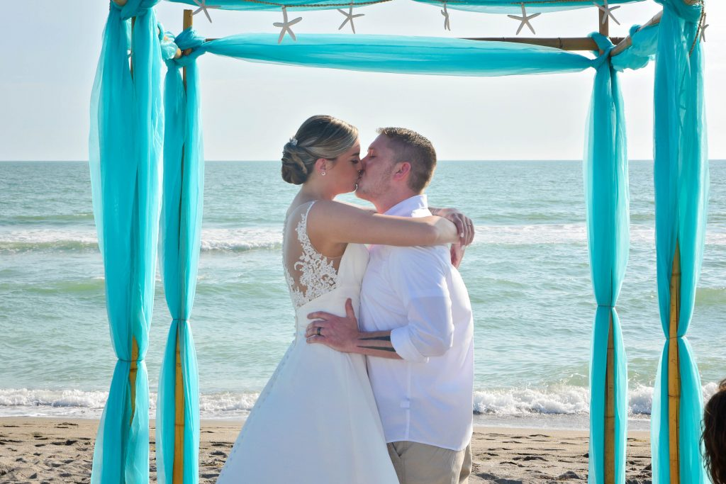 Couple kisses on St. Augustine beach under teal wedding arch with starfish