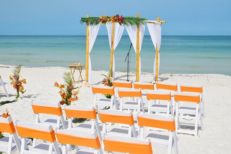 Tropical Wedding Arch on the beach with flowers and white chairs St. Pete