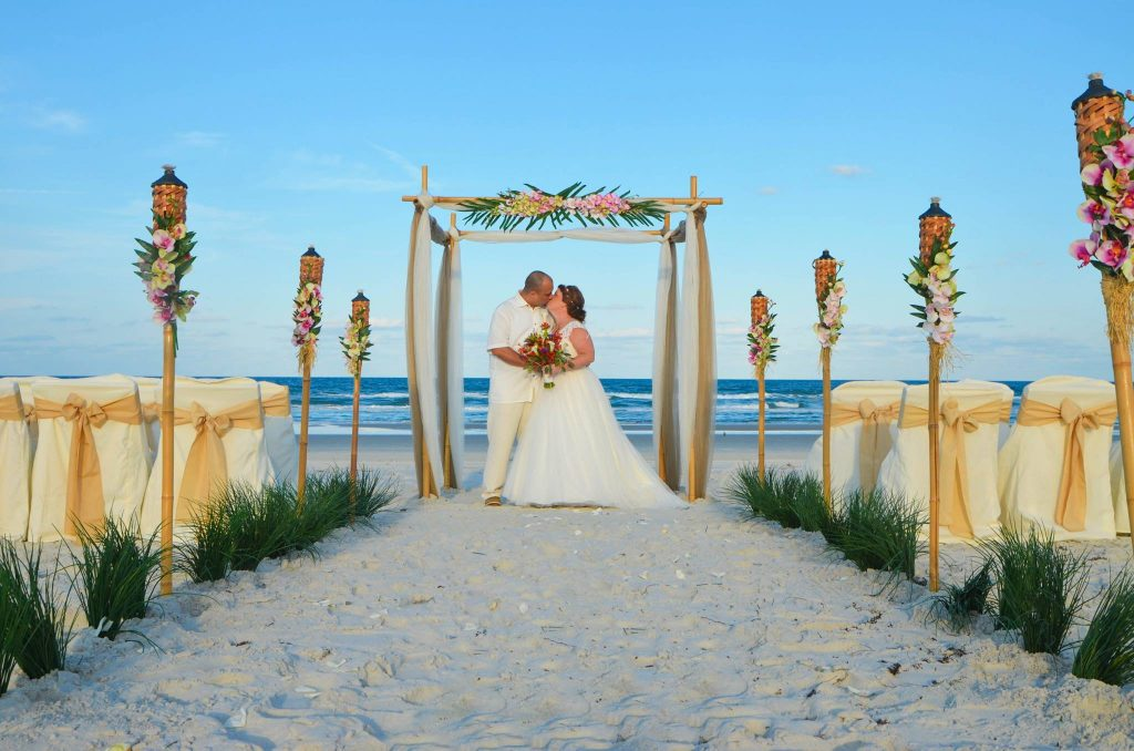 Beach marriage under tropical bamboo canopy with couple kissing